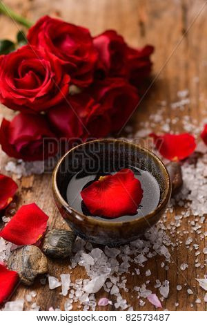 Lying down roses with petals in bowl with pile of salt ,stones on old wooden board