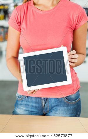 Midsection of mid adult woman holding digital tablet in hardware shop