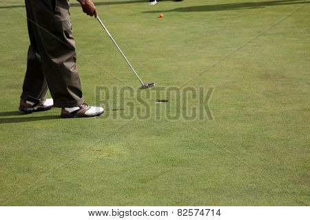 Golfer, Man swinging golf club with and driving the golf ball with extreme accuracy and skill sinking a HOLE IN ONE on 7 of the 9 holes he played. Golf is loved by millions around the world