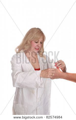 a nurse in a lab coat bandages a persons hurt thumb isolated on white with room for your text. nurses and doctors around the world help with people who have sore thumbs from various reasons daily.