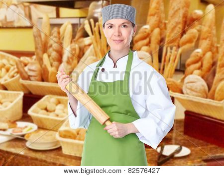 Young professional baker woman in modern bakery.