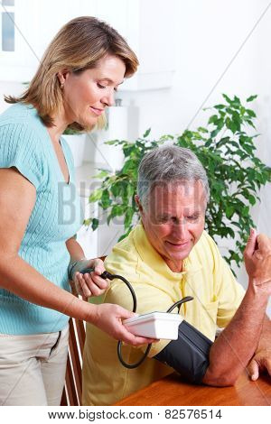 Senior woman and man measuring blood pressure.