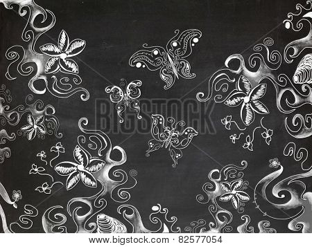 Drawings of various butterflies and floral patterns on chalk board
