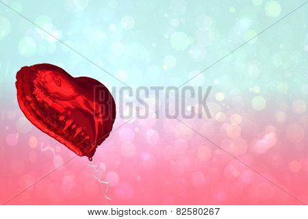 Red heart balloon against blue and pink light spot design