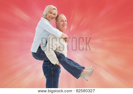 Happy mature couple having fun against red abstract light spot design