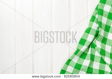 Green towel over wooden kitchen table. View from above with copy space