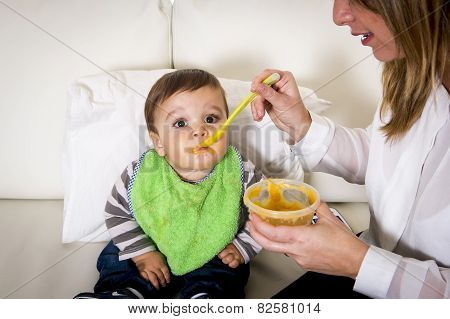 Mother With Spoon Porridge Feeding Sweet Little Son In Messy Bib Mush Stains