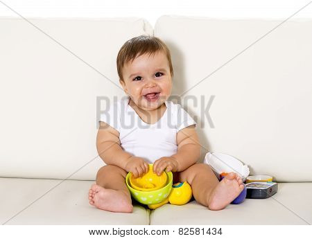 Sweet Cute Little Baby Sitting On Couch Alone At Home Playing With Toys Happy And Relaxed Having Fun