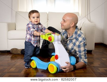 Young Father And Little Son Walking With Baby Walker Taking His First Brave Steps