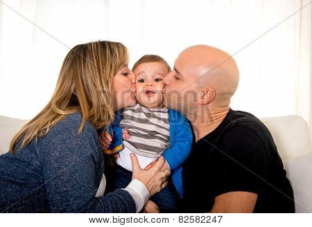 Young Hispanic Happy Mother And Father Kissing Little Son Couch Together Smiling With Sweet Baby Boy