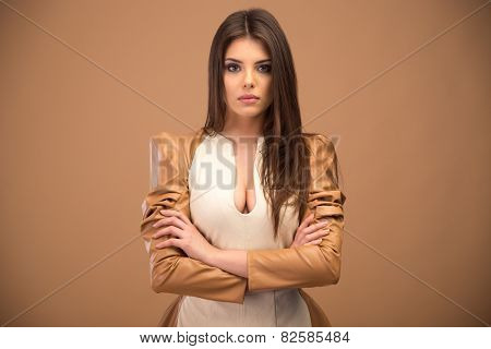 Portrait of attractive young woman with arms folded over brown background