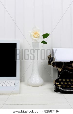 Closeup of a white desk with a bud vase between a modern laptop computer and an antique typewriter. Only half of the laptop and typewriter are shown. Vertical format.