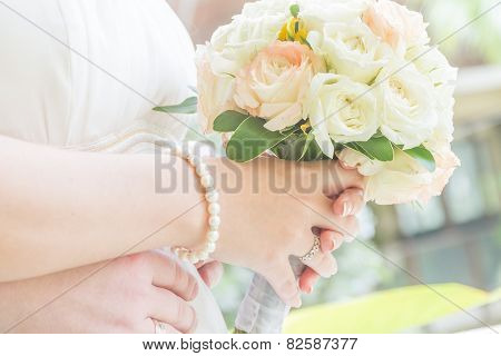 wedding bouquet in bride's hands on outdoor natural background