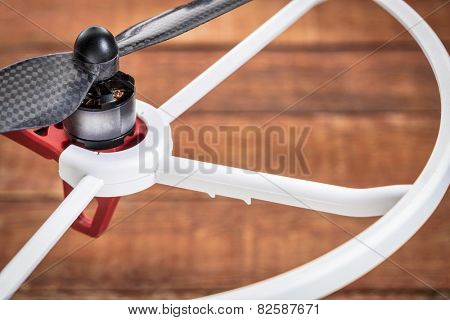 a detail of drone electric motor, carbon fiber propeller and propeller guard over wood background