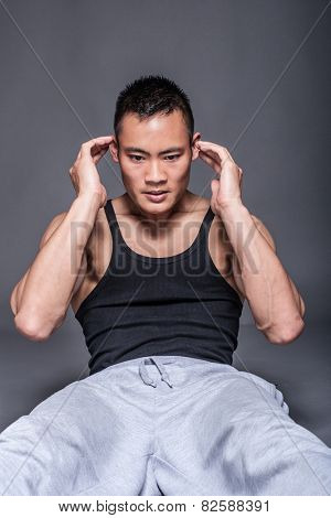 Young asian man workout over grey background - abdominal crunch