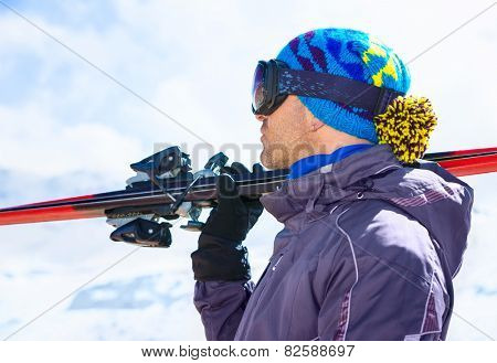Side view of handsome skier man wearing mask and holding ski equipment in hand, having fun on the mountains, active winter vacation concept