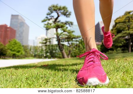 Running shoes - woman runner jogging staying fit in Tokyo Park, Japan. Closeup of pink trainers in green grass in summer park near the Imperial Palace and Ginza district downtown.