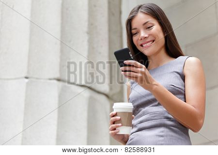 Young smart professional woman reading using phone. Female businesswoman reading news or texting sms on smartphone while drinking coffee on break from work. Mixed race asian caucasian business woman.