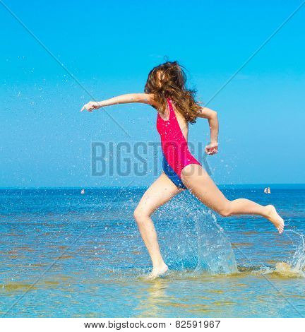 Woman running in shallow seawater on Vacation