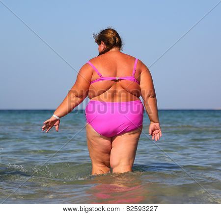 overweight woman bath in sea - view from back