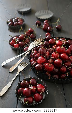 Fresh  cherries in aluminum plates on table