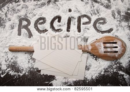 Word recipe written in white flour and spatula on wooden table