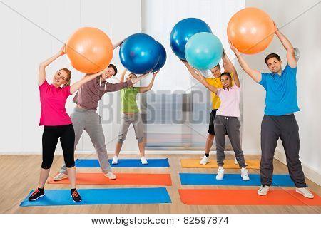 Group Of People Lifting Pilates Ball