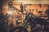 picture of carburetor  - Mechanic doing lathe works in motorcycle customs garage  - JPG