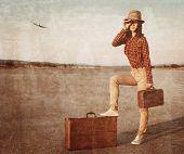 image of binoculars  - Tourist woman with vintage suitcase looking through binoculars on road airplane in sky - JPG