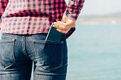 picture of denim jeans  - Woman takes out smartphone of her rear pocket of jeans on beach near the sea to make self - JPG