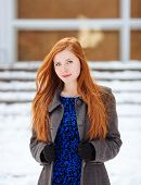 stock photo of redhead  - Portrait of young beautiful redhead woman in blue dress and grey coat at winter outdoors - JPG
