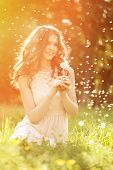 image of allergy  - Young spring fashion woman blowing dandelion in spring garden - JPG