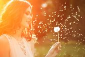 stock photo of dandelion  - Young spring fashion woman blowing dandelion in spring garden - JPG