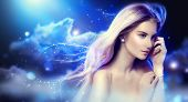 stock photo of blowing  - Beauty fantasy girl with long blowing hair over night sky with stars - JPG