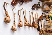 picture of tobacco smoke  - traditional wooden smoking tobacco pipe hanging on white wall - JPG