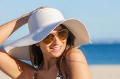 pic of beach hat  - smiling summer woman on beach with sunglasses and floppy hat - JPG