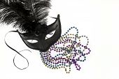image of debauchery  - Shiny gold purple blue and silver beads and Mardi Gras mask with feathers on a white background - JPG