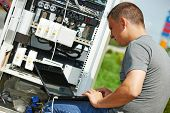 picture of telecommunications equipment  - engineer working with laptop outdoors adjusting communication equipment in distribution box - JPG