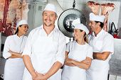picture of slaughterhouse  - Portrait of happy mature male butcher with team in butchery - JPG