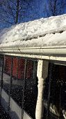 foto of snow shovel  - Man shovelling snow from a roof in Sweden - JPG