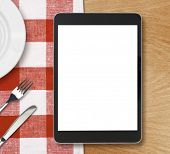 foto of blank check  - black tablet pc or ipad on dinner table with blank screen - JPG