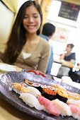 pic of plate fish food  - Sushi eating woman tourist in Tokyo restaurant - JPG