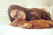 pic of sleeping  - Cute ginger cat sleeps near kid girl on the sofa - JPG