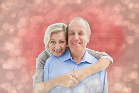 picture of male pattern baldness  - Happy mature couple embracing smiling at camera against light glowing dots design pattern - JPG