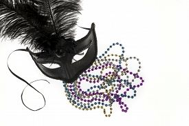 foto of debauchery  - Shiny gold purple blue and silver beads and Mardi Gras mask with feathers on a white background - JPG