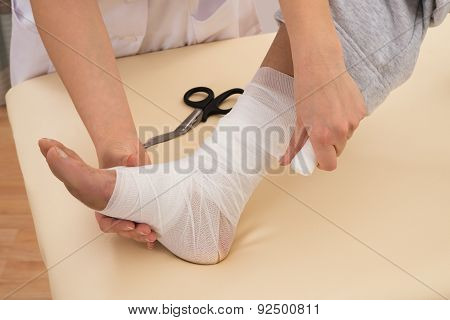 Nurse Wrapping Bandage On Patient's Foot