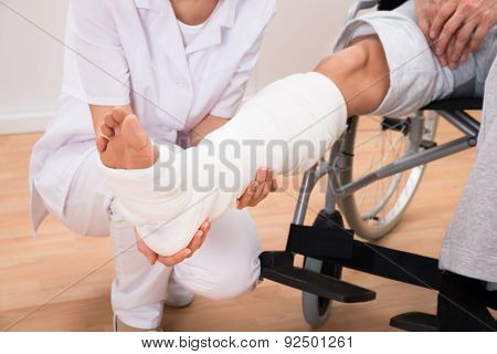 Female Doctor Holding Patient's Leg