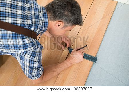 Worker Drawing A Mark On Laminate Using Ruler