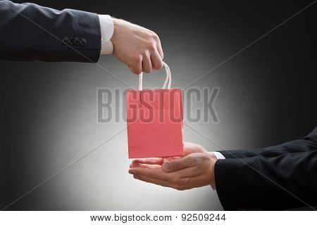 Two Businessmen Hands With Small Bag