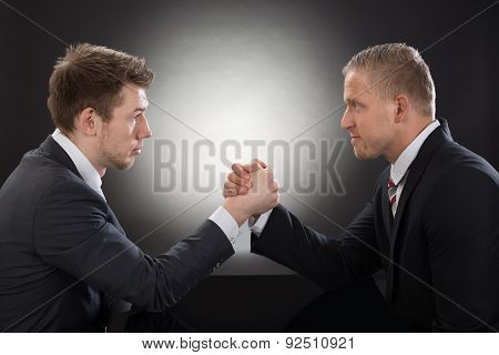 Two Young Businessman Arm Wrestling